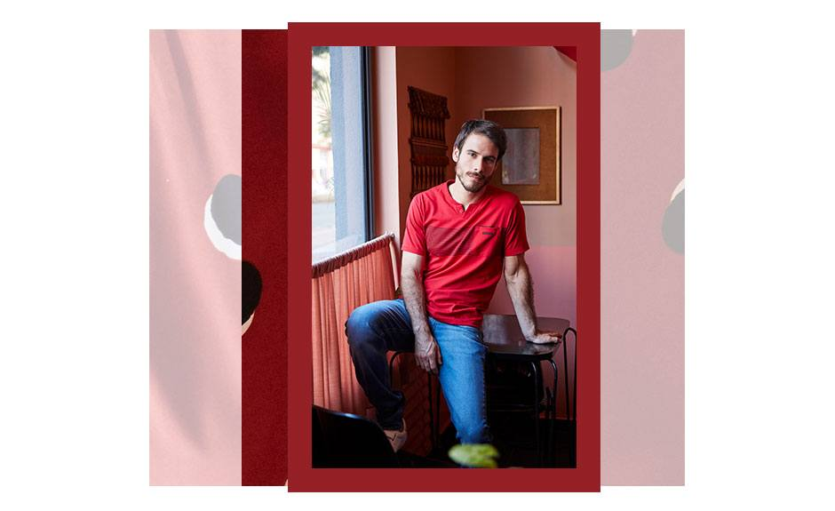 Camiseta masculina vermelha com detalhe em listras e calça jeans básica.