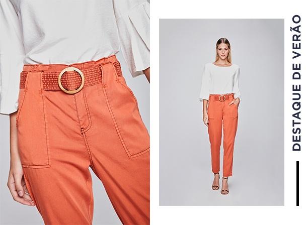 Calça de sarja laranja com cinto de fivela e blusa branca.