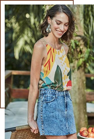 Regata de tiras com estampa floral maxi e saia mini jeans com tachas na lateral e barra desfiada.