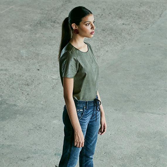 Blusa feminina de manga curta em material sintético verde militar e calça jogger jeans escuro.