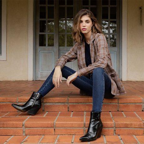 Calça jeans skinny azul escuro, camiseta preta e casaco xadrez em tons de marrom e bege.