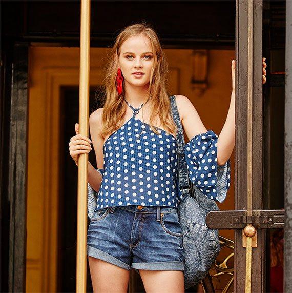 Short jeans com a barra dobrada e blusa azul de estampa de poás brancos, decote com tira amarrada no pescoço e mangas sino.
