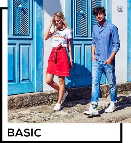 Saia midi vermelha com cinto e camiseta branca com tipografia e detalhe de ribana vermelha nas mangas, calça jeans masculina clara com camisa social azul.