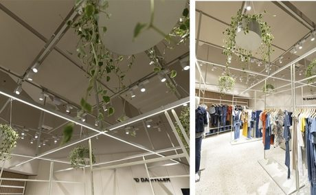 Detalhes das folhagens usadas no teto da loja e da iluminação em LED, araras com as peças.