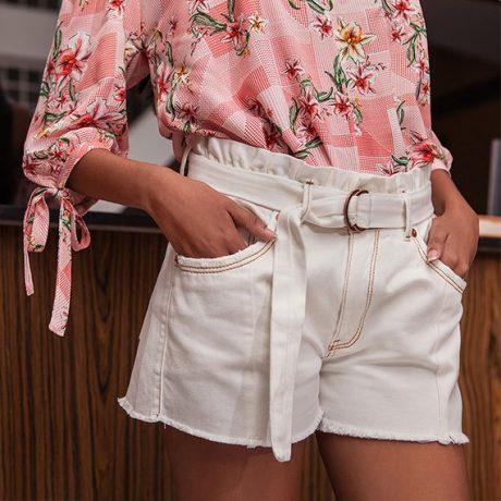 Short clochard jeans off white e blusa estampada com flores e pequenos xadrez em vermelho e branco com detalhe de amarração na manga 3/4.