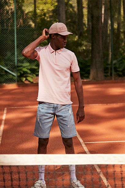 Bermuda masculina jeans clara e camisa de gola polo rosa claro e boné.