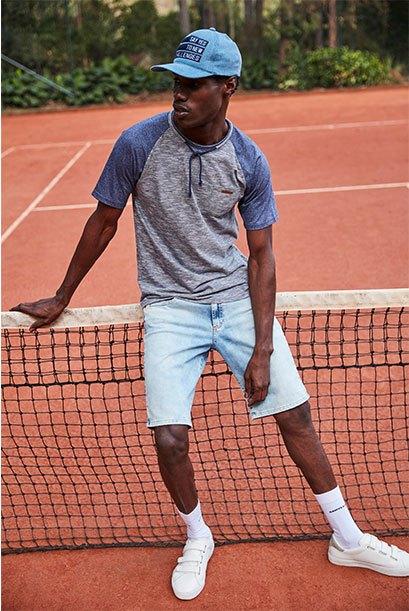 Bermuda masculina jeans claro, camiseta em cinza mescla e detalhe de mangas azuis, boné.