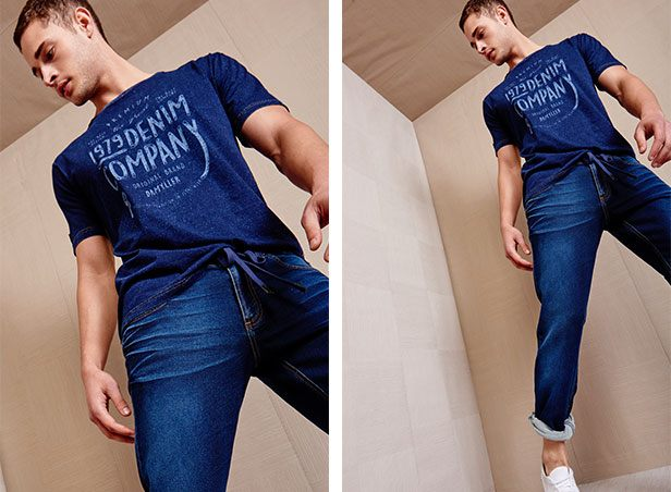 Calça jeans jogger azul escuro e camiseta de malha denim azul escuro com serigrafia centralizada.