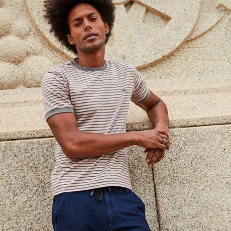 Camiseta masculina de malha listrada em tons de bege e cinza com detalhe de ribana nas mangas e gola com calça jogger azul escuro.
