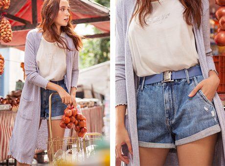 Short jeans de cintura alta com cinto azul claro, camiseta branca com tipografia centralizada e cardigã alongado cinza claro.
