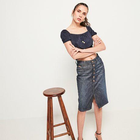 Saia midi jeans escuro com botões frontais e abertura, top cropped azul marinho em sued, mangas bufantes e decote quadrado.