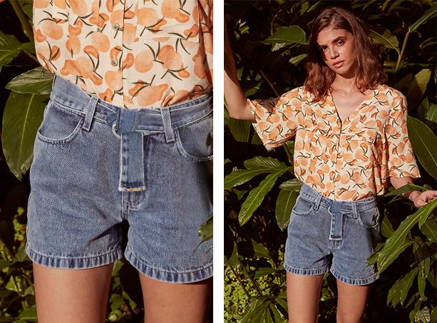 Short jeans claro de cintura alta com cinto também em jeans usado com amarração em nó e camisa com fundo claro com estampa de frutas cítricas., manga 3/4.