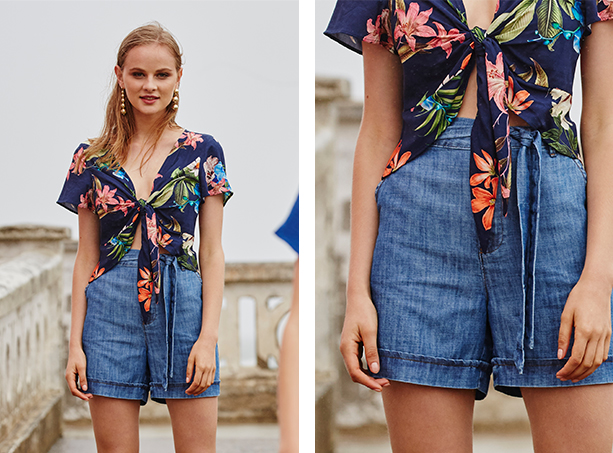 Top cropped azul com estampa de flores e amarração frontal, short jeans leve de cintura alta com cinto em jeans e barra dobrada.