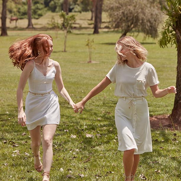 Vestido médio branco de alcinhas com detalhe de cinto em corda com pingentes de frutos do mar. Saia midi branca e camiseta de malha com detalhe de bolso no lado esquerdo com pingentes.