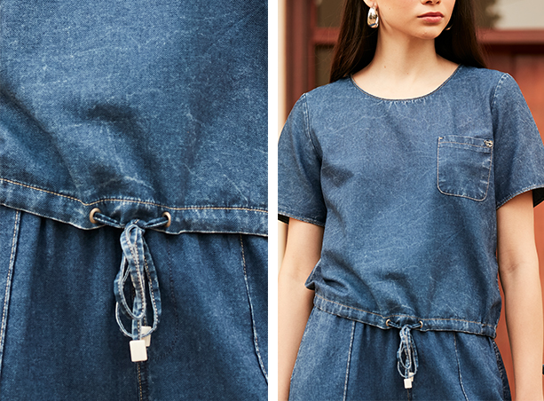 Blusa jeans escuro com cordão interno na parte de baixo e detalhe de bolso na lateral esquerda e calça jeans escuro.