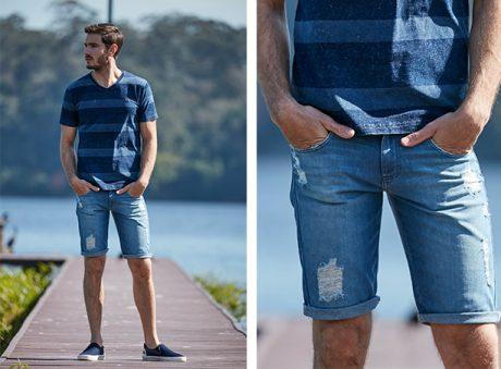 Bermuda masculina jeans claro com detalhe de rasgos e com a barra dobrada, camiseta de malha denim com listras azul escuro com azul claro.
