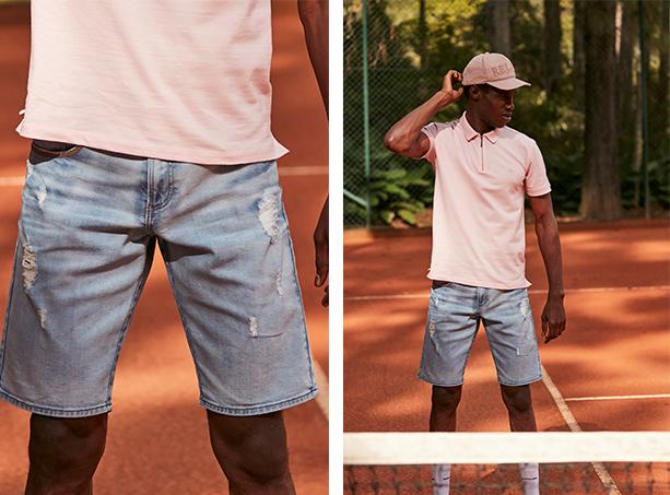 Bermuda masculina jeans claro com desgastes e camisa gola polo rosa claro e boné claro.