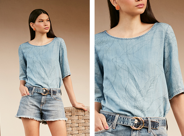 Short mini jeans claro com barra desfiada e cinto jeans com fivela e blusa jeans claro com estampa em azul de folhagens, mangas 3/4.