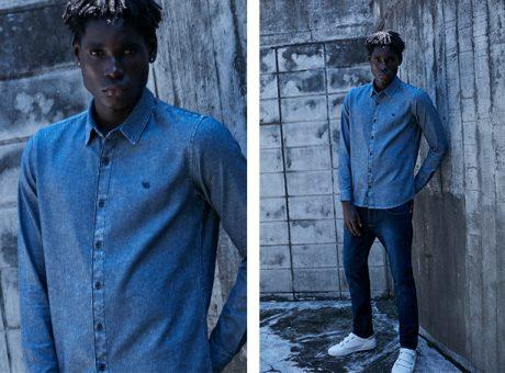 Calça masculina em jeans escuro com camisa jeans escuro de manga longa usada toda fechada.