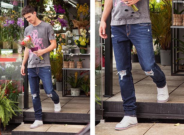 Calça jeans masculina cor escura com rasgos nos joelhos