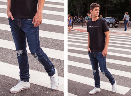 Calça masculina jeans escuro com rasgos nos joelhos, camiseta preta com frase em branco centralizada.