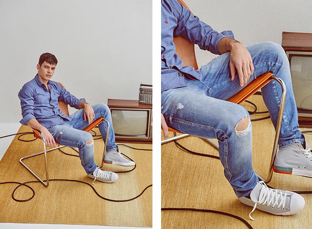 Camisa social masculina azul e calça jeans claro com rasgos.
