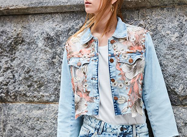 Jaqueta feminina jeans claro com flores beges bordadas e pérolas.