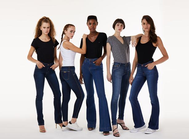 Diferentes modelagens e lavações de calças jeans femininas com blusas pretas, cinza e branco.