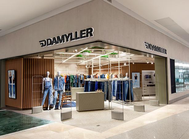 Foto da entrada e frente da loja, manequins e peças expostas.