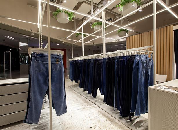 Foto do detalhe das lâmpadas de LED com as calças jeans expostas na loja.