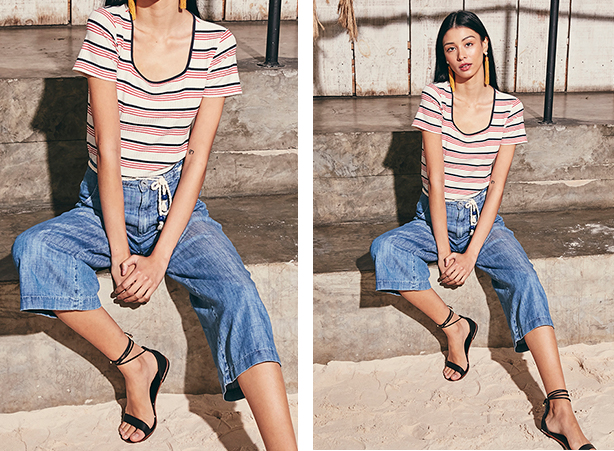 Camiseta de malha com listras azul e vermelho com detalhe de ribana azul e calça pantacourt jeans claro e detalhe de cinto de corda.