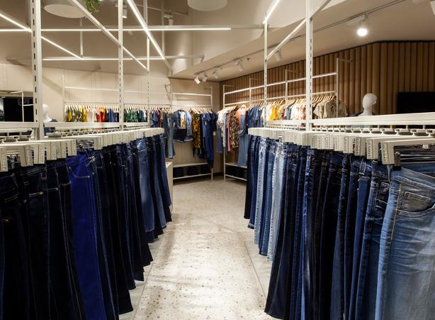Foto dos expositores de calças jeans e das peças em malhas.