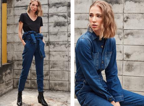 Macacão jeans escuro com a parte de cima amarrada na cintura com uma camiseta preta básica. Macacão jeans escuro usado todo fechado por abotoamento de botões e detalhe de bolsos dianteiros.