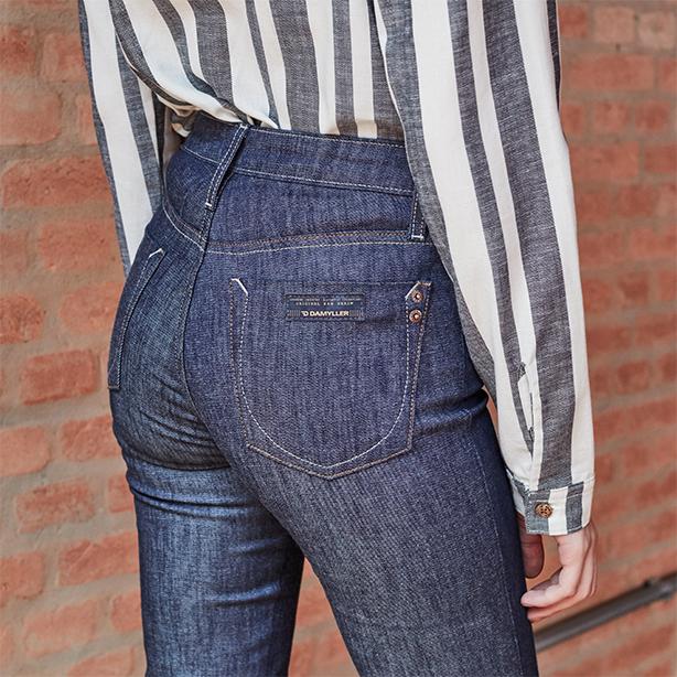 Calça feminina jeans escuro com detalhe do bolso traseiro e camisa off white com listras em azul e manga comprida.