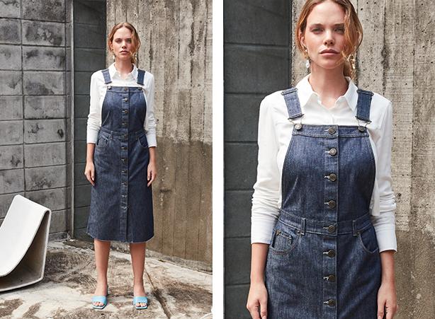 Jardineira saia midi jeans escuro com abotoamento frontal e barra desfiada com camisa branca de mangas longas.