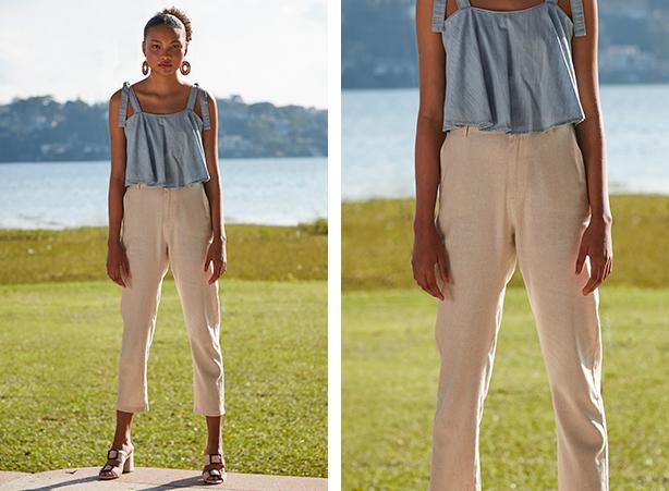Calça feminina bege de alfaiataria com top cropped jeans claro com as alças usadas com amarração.
