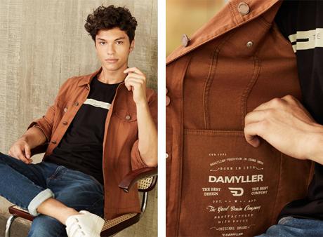 Calça masculina jeans skinny com a barra dobrada, camiseta preta com listra centralizada bege com escrita e jaqueta camelo com bolso interno com silk.