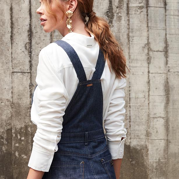 Jardineira saia midi jeans, detalhe das costas e camisa branca de mangas longas para compor o look.