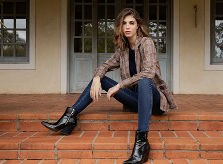 Calça feminina jeans escuro cropped, camiseta preta e blazer alongado xadrez de mangas longas sobreposto a camiseta.